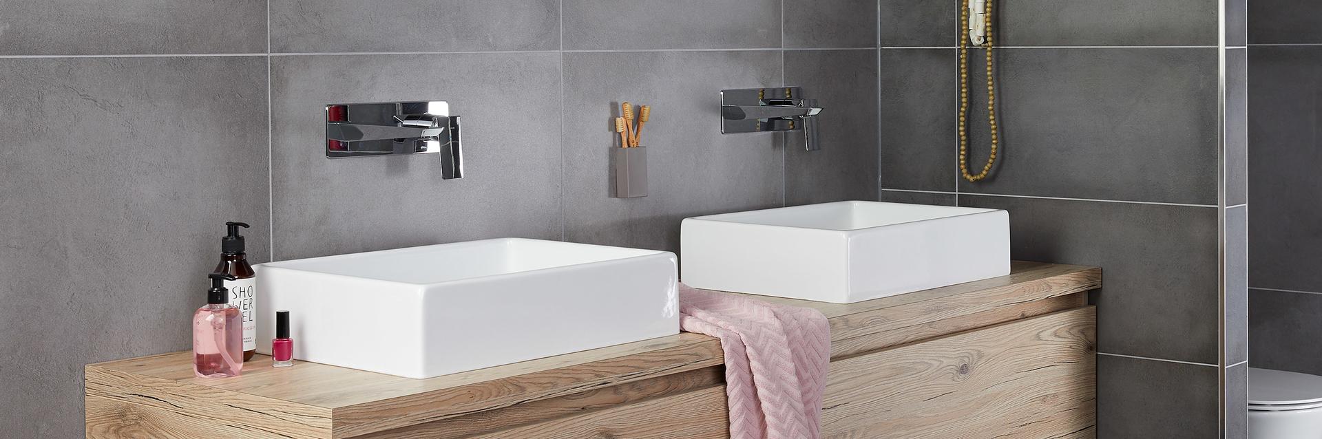 Inbouwkraan in betonlook badkamer met hout meubel en strakke opzetkommen