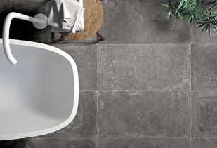 Betonlook tegels met wit bad en witte kraan
