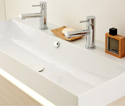 Familie badkamer met brede wastafel en twee kranen