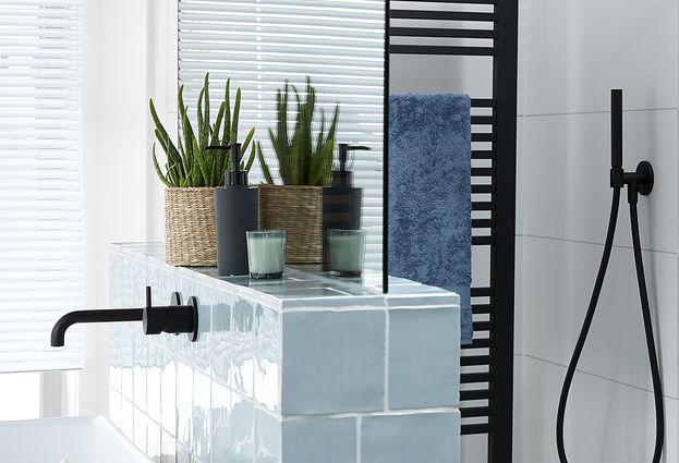 Moderne badkamer met zwarte kraan, radiator en douche